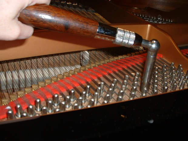 piano_tuning_lever_that_is_on_a_tuning_pin_with_hammer_striking_a_string_in_an_acoustic_grand_piano